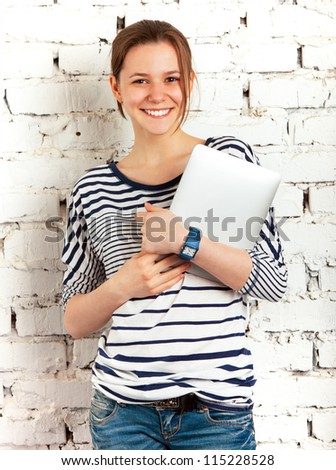 Teenager schoolgirl with tablet computer near the white brick wall