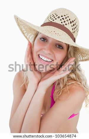 Teenager showing a great smile with her hands on her cheeks against a white background