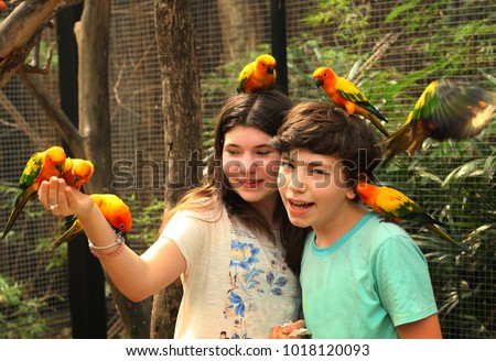 teenager siblings boy and girl in open air zoo with parrots sit on hand and head smiling portrait