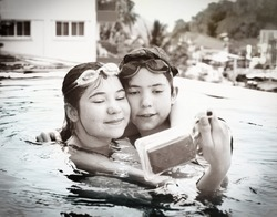 teenager siblings brother and sister make selfie in the swimming pool with special waterproof camera close up photo