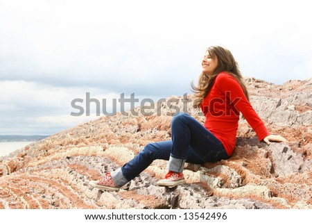 Teenager sit on a rocks and enjoy the day