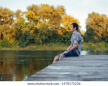 teenager sits on a wooden bridge by the river outdoor and looks in the Wake of the departing summer. Last summer days