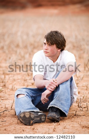 teenager sitting amongst the weeds in a dry lake bed. Natural-looking teen, simple clothing, ripped jeans, shot in Wyoming with copyspace.