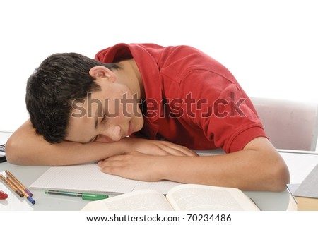 Teenager sitting at a desk and does his homework, he is tired and exhausted, isolated against a white background.