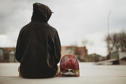 Teenager sitting in a black sweatshirt holding a skateboard on a slum background urban