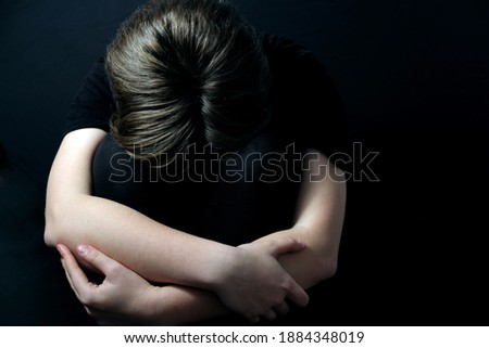 teenager sitting in a closed posture experiencing mental health problems such as depression during COVID-19 lockdown Foto stock ©