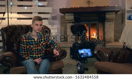 Teenager sitting in front of home video camera and speaking something during shooting. His has tablet in his hand and sits near the fireplace