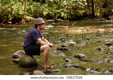 Teenager sitting on river rocks, with hat on, side view
