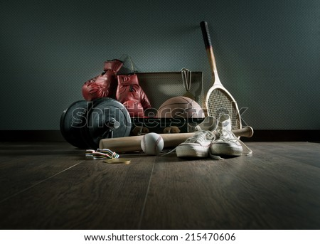 Teenager sport equipment in a vintage suitcase including sports footwear, boxing gloves, weights and baseball bat.