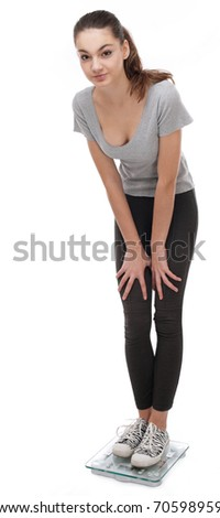 Teenager standing on scales. Isolated on a white background.