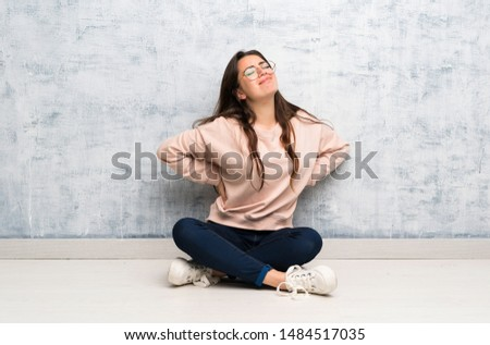 Teenager student girl studying in a table suffering from backache for having made an effort