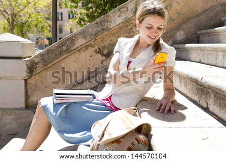 Teenager student using her smart phone while sitting down at a college stone steps during a sunny day, smiling.