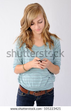 Teenager Texting on Smartphone. Thirteen year old girl looking at her smartphone while texting. Note: Not Isolated.