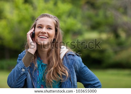 Teenager using her cellphone while showing a beaming smile