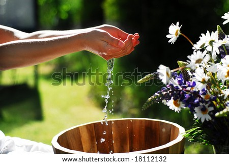 Teenager washing hands in the garden