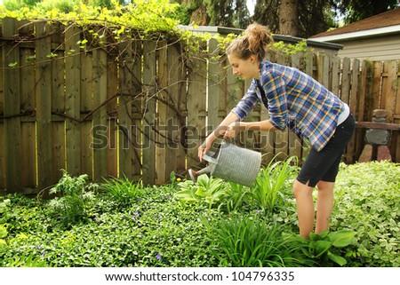 Teenager watering flowers in their garden