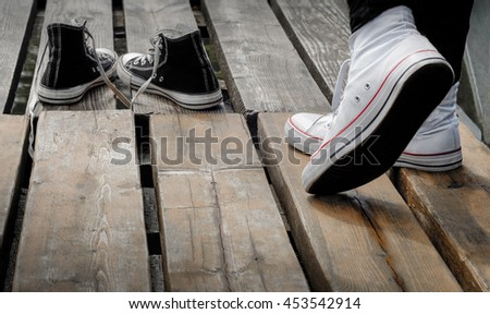 Teenager wearing white shoes standing behind black snickers on the wooden bridge, choice concept #453542914