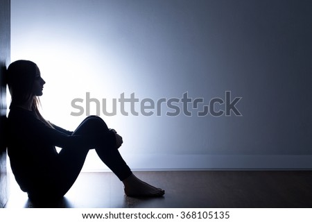 Shutterstock Teenager with depression sitting alone in dark room
