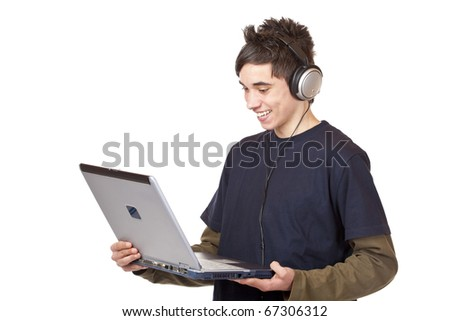 Teenager with headset makes internet mp3 music download at computer. Isolated on white background.