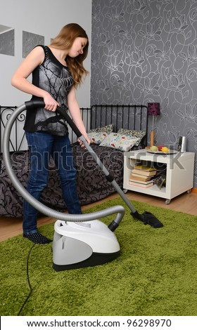 Teenager with vacuum cleaner