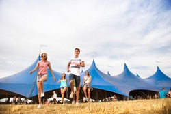 Teenagers at summer music festival in front of big blue tent