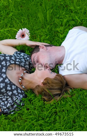 Teenagers: girl and fellow are lying on green grass and kissing. Green grass around them and flower