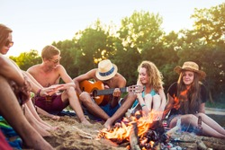 Teenagers having fun at the beach. They are sitting in the sand in circle around a camp fire, wearing short pants, sunglasses and straw hats. They are singing and a boy is playing guitar