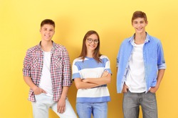 Teenagers in casual clothes on color background