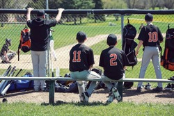 Teenagers in dugout behind chainlink fencing, shallow focus