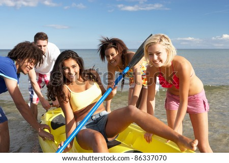 Teenagers in sea with canoe