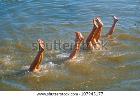 Teenagers legs upside down in the river on sunny summer day.
