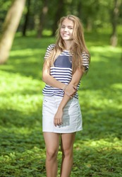 Teenagers Lifestyle Concepts. Portrait of Blond Caucasian Teenager Girl Posing Outside in Green Forest.Vertical Image