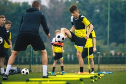 Teenagers on soccer training camp. Boys practice football witch young coaches. Junior level athletes improving soccer skills on outdoor training. Player kick soccer ball to coach and ladder skipping