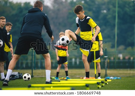 Teenagers on soccer training camp. Boys practice football with young coaches. Junior level athletes improving soccer skills on outdoor training. Player kick soccer ball to coach and ladder skipping