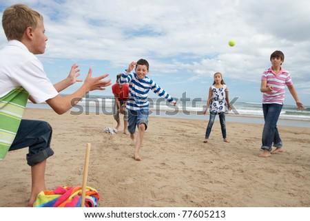 Teenagers playing baseball on beach - stock photo