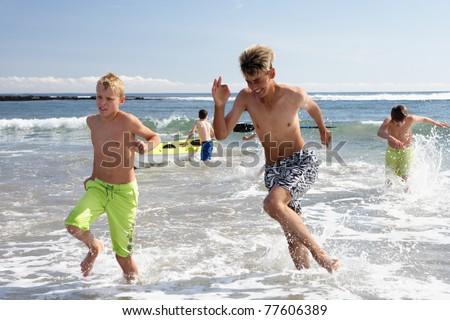 Teenagers playing on beach - stock photo
