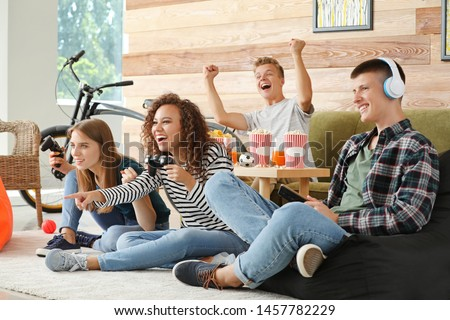 Teenagers playing video game at home #1457782229