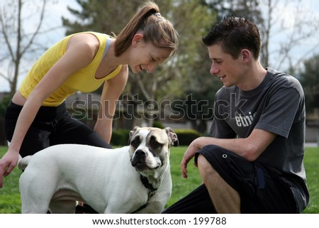 Teenagers playing with a dog in the park