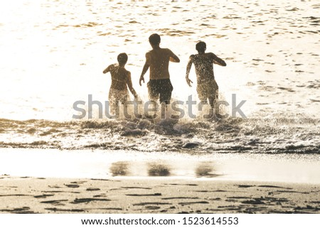 Teenagers running in the water of the ocean at sunset. Group of teen enjoying break of school jumping happy in the sea. People enjoy holiday having fun together at the beach Vacation happiness concept #1523614553