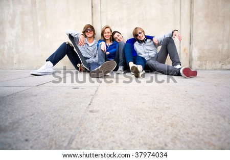 Teenagers Sitting by a Wall