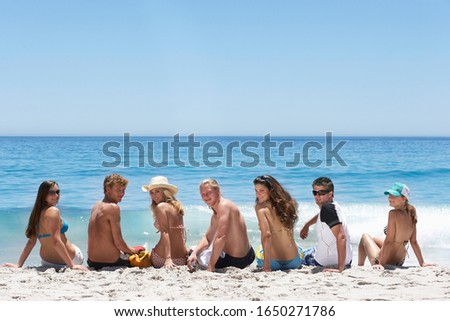Teenagers (16-18) sitting on beach, looking over shoulder, portrait