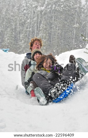 Teenagers sledding in the snow on a saucer. Winter fun.