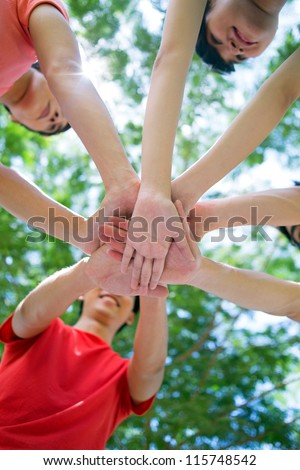 Teenagers stacking their hands