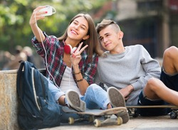teenagers taking picture of themselves for selfie with phone
