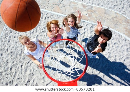 Teenagers team playing street basketball - stock photo