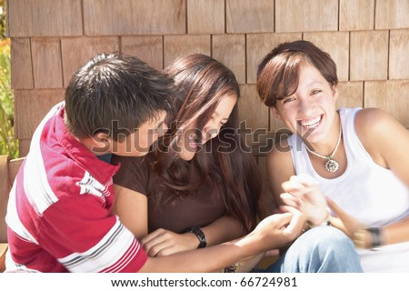 Teenagers tickling each other
