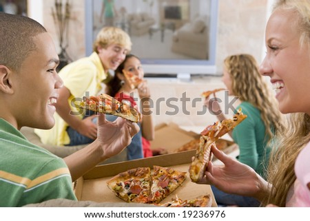 Teenagers Watching TV And Eating Pizza