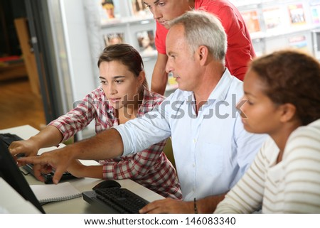 Teenagers with teacher in computers class