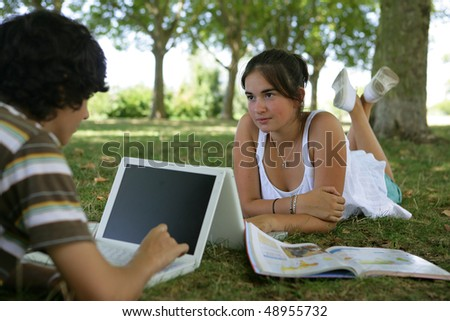 Teenagers working on laptop in a park