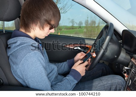 Teens in the car-phone use - stock photo